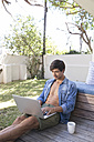 Man sitting on terrace in garden using laptop - WESTF23170
