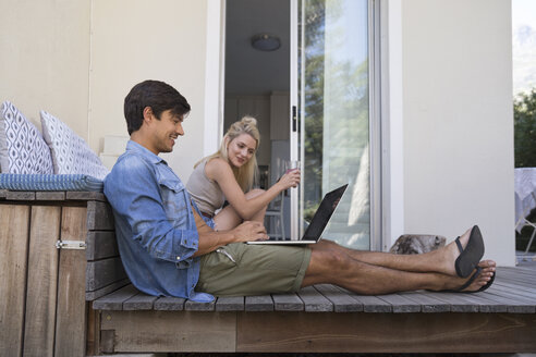 Young couple sitting on terrace with man using laptop - WESTF23173