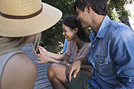 Smiling woman showing cell phone to friends on veranda - WESTF23188