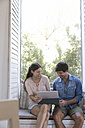 Smiling young couple sitting on windowsill sharing tablet - WESTF23197