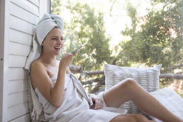 Laughing young woman wrapped in a towel holding cell phone - WESTF23200