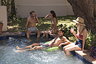 Group of friends relaxing at swimming pool - WESTF23209
