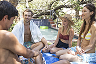 Group of friends relaxing in garden at the poolside - WESTF23221