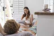 Smiling young woman with laptop looking at man - WESTF23245