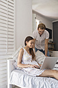 Smiling young couple with laptop in bedroom - WESTF23248