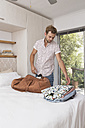 Young man packing bag in bedroom - WESTF23263