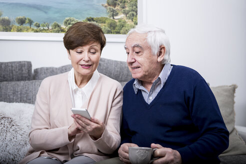 Senior couple lying on couch using smartphone - WESTF23287