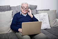 Senior man sitting on couch, using laptop and smartphone - WESTF23299
