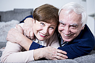 Senior couple lying on couch, hugging - WESTF23305