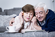 Senior couple lying on couch, listening music from digital tablet - WESTF23308