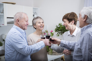 Two senior couples celebrating, toasting with red wine - WESTF23377