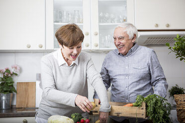 Senior couple standing in kitchen, unpacking fresh vegetables - WESTF23380