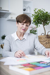 Senior woman drawing picture with crayons - WESTF23395