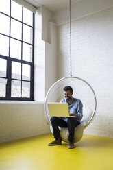 Smiling man sitting on swing in his loft using laptop - ABZF02040
