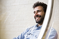 Portrait of smiling young man with beard - ABZF02043