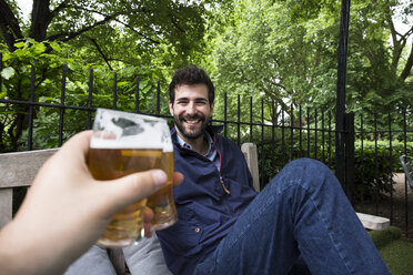 Portrait of smiling young man toasting with glass of beer in garden - ABZF02076