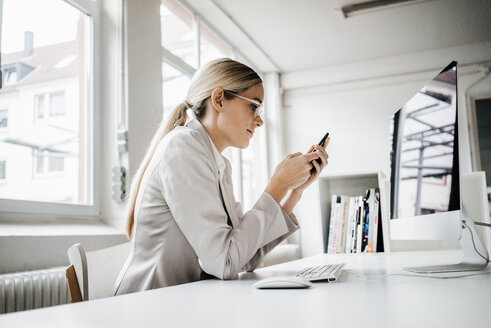 Businesswoman sitting at desk using cell phone - JOSF01059