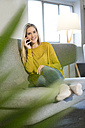 Portrait of smiling young woman on the phone at home - JOSF01065