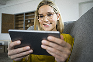 Portrait of smiling woman with glasses sitting on couch using mini tablet - JOSF01068