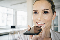Portrait of smiling businesswoman using cell phone - JOSF01071