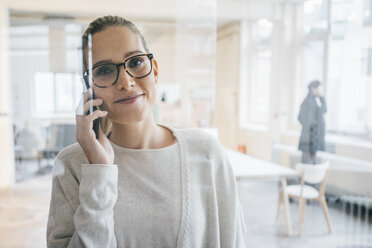 Portrait of smiling businesswoman on the phone in the office - JOSF01074