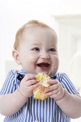 Portrait of happy baby boy with muffin - FSF00922