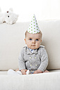 Portrait of serious baby boy wearing paper hat - FSF00925