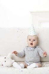 Portrait of amazed baby boy wearing paper hat - FSF00928
