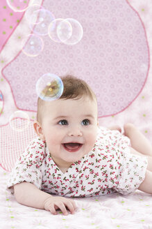 Portrait of amazed baby girl watching soap bubbles - FSF00940