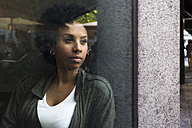 Portrait of young woman looking out a window in a cafe - ABZF02084