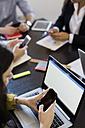 Business people using cell phones during a meeting in office - GIOF02654
