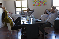 Business people leaning back during a meeting in office - GIOF02663