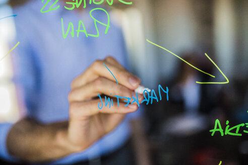 Businessman writing on glass wall - GIOF02684