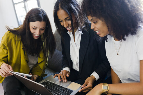 Three smiling businesswomen sharing laptop in office - GIOF02705