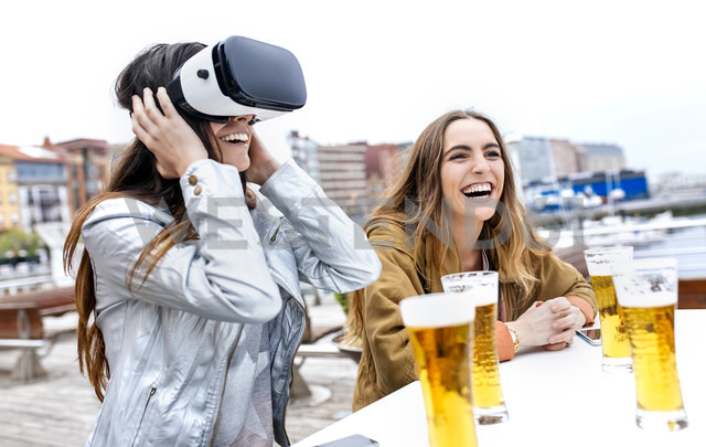 Two young women having fun with VR glasses in the city - MGOF03422 - Marco Govel/Westend61