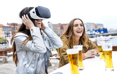 Two young women having fun with VR glasses in the city - MGOF03422