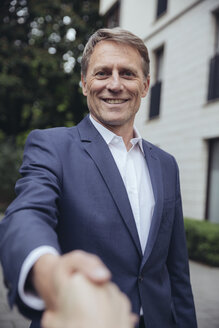 Portrait of smiling mature businessman shaking hands outdoors - MFF03611