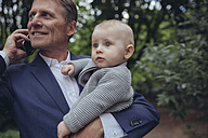 Mature businessman holding his baby and talking on smartphone - MFF03614