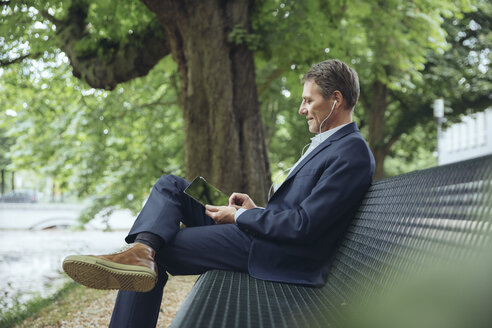 Smiling mature businessman sitting on park bench with tablet and earphones - MFF03617