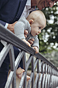 Father holding his baby to look over a fence - MFF03620