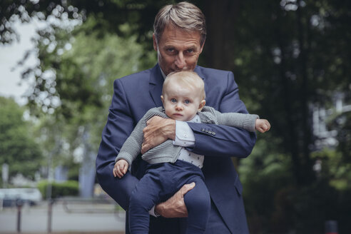Portrait of mature businessman holding baby boy outdoors - MFF03623