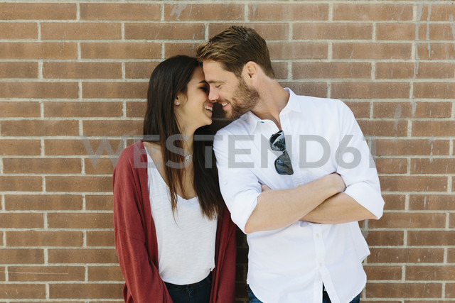 Happy couple standing in front of brick wall, kissing - GIOF02713