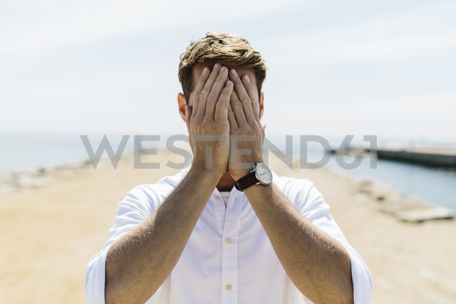 Mid adult man on the beach covering eyes - GIOF02731