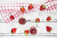 Two glasses of homemade strawberry jam, kitchen towel and strawberries on white wood - LVF06152