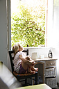 Little girl sitting on chair looking out of window - FKF02333