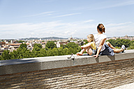 Italy, Rome, mother and her little daughter sitting back to back on a wall looking at view - FKF02336