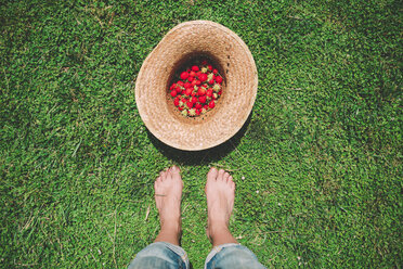 Barefoot woman standing next to straw hat full of strawberries on the lawn - GEMF01661