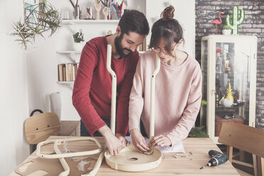 Young couple assembling flat-pack stool at home - RTBF00889