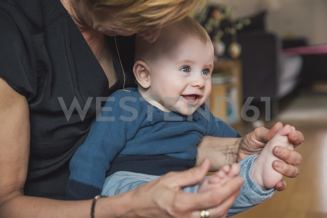 Woman playing with baby boy's feet at home - MFF03627