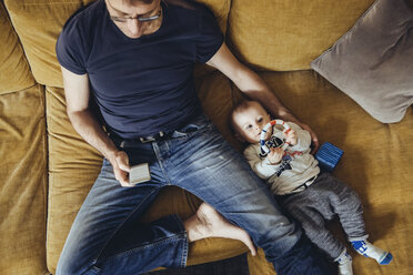 Baby boy lying on couch besides his father using smartphone - MFF03630